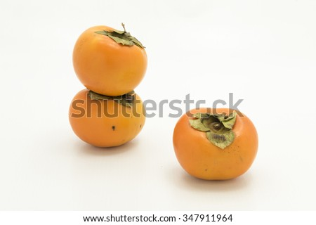 Side view of three persimmon fruits.  Isolated on white background..