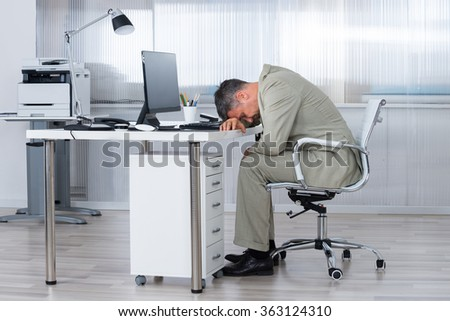 Side view of tired businessman sleeping on desk in office - stock photo