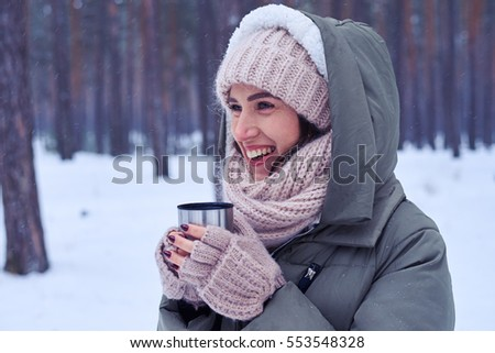 Side view of toothy smiling model with a cup of coffee looking sideways. Wearing modern winter outfit on a sunny snowy day