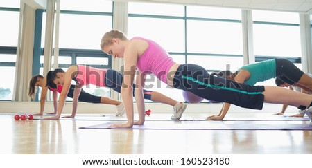 Side view of trainer with class doing push ups in bright fitness studio - stock photo