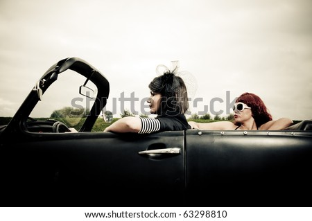 Side view of two attractive girls driving around in vintage car - stock photo