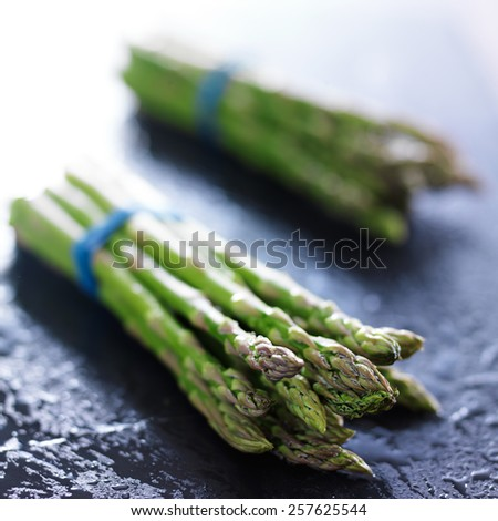 side view of two bunches of fresh asparagus - stock photo