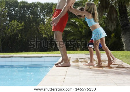 Side view of two children pushing cropped father into swimming pool - stock photo