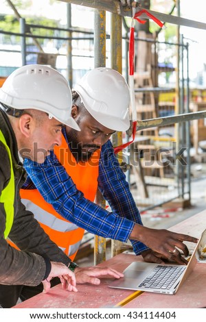 Side view of two engineers, an african american and a white, wearing orange and yellow safety jackets and helmets, working with laptop computer among scaffolding on construction site. Vertical shot