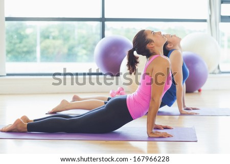 Side view of two fit women doing the cobra pose in a bright fitness studio - stock photo