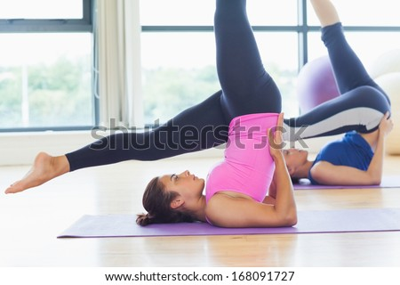 Side view of two fit women doing the shoulder stand posture in fitness studio