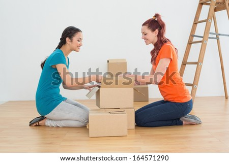 Side view of two friends moving together in a new house and unwrapping boxes - stock photo