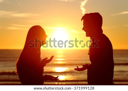 Side view of two friends or couple silhouette of teens talking happy on the beach at sunset with the sun in the middle and a warmth light - stock photo