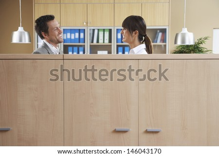 Side view of two office workers talking behind cubicle - stock photo