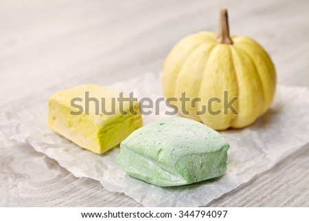 Side view of two pastel marshmallows and small pumpkin on white craft paper wooden table