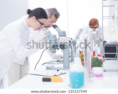 side-view  of two scientists in  a chemistry lab analyzing under microscope on a lab table around lab tools - stock photo