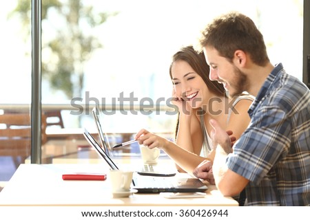 Side view of two young adult students studying and talking about lessons comparing together laptop information in a coffee shop - stock photo