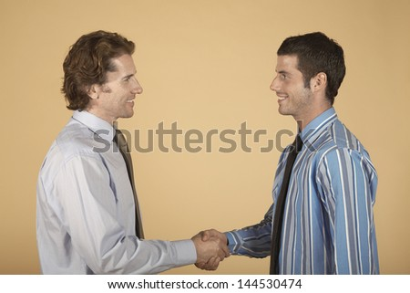 Side view of two young businessmen shaking hands on colored background - stock photo