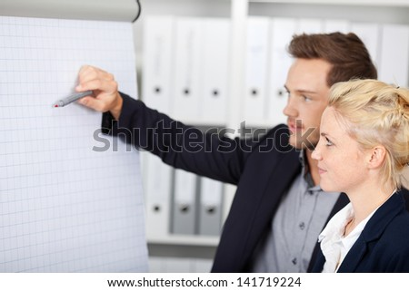 Side view of two young businesspeople working on flipchart at office - stock photo
