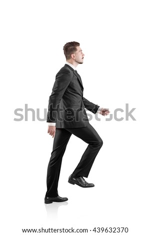 Side view of walking businessman in suit isolated on white background - stock photo