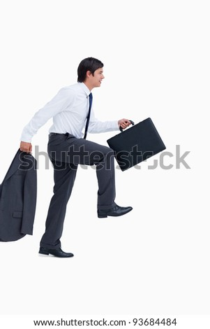 Side view of walking tradesman with jacket and suitcase against a white background - stock photo