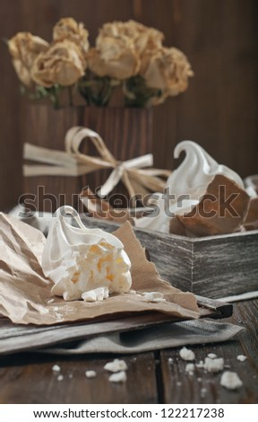 Side view of white broken meringue, wooden box with meringue and dry roses in a wooden square vase - stock photo