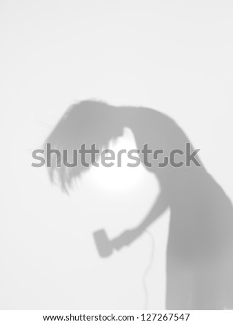 side view of woman drying her hair with a hair drier behind a diffuse surface