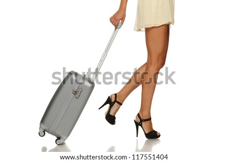 Side view of woman legs with a suitcase on the white background - stock photo