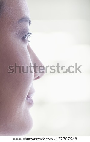Side view of woman's face on bright background