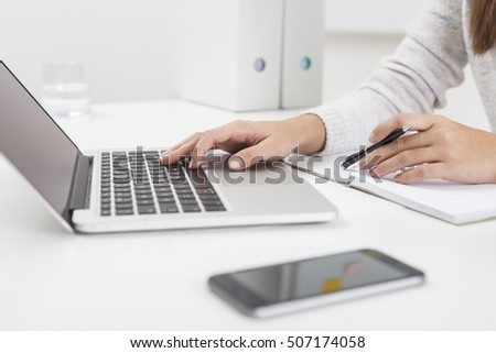 Side view of woman's hands. She is typing and holding a pen. White binders are seen at the background. Concept of office work.