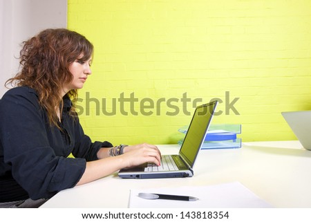 Side view of woman working at her computer