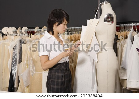 Side view of woman working in her clothing store - stock photo