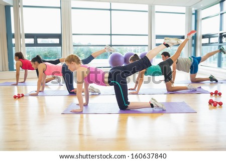 Side view of women stretching on mats at yoga class in fitness studio - stock photo