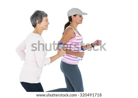 Side view of women with bottle jogging against white background - stock photo
