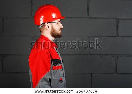 side view of worker wearing overalls and red helmet and protection eyeglasses
