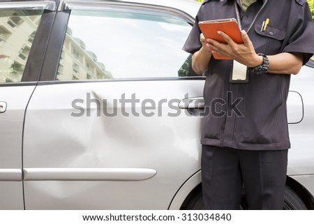 Side view of writing on tablet computer  while insurance agent examining car after accident - stock photo