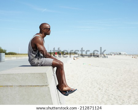 Side view of young african man sitting on a beach promenade looking away. Afro american model relaxing outdoors at beach with copyspace.  - stock photo