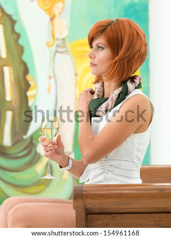 side view of young attractive redhead woman sitting and holding a glass of wine in her hand, looking in front of her, with colorful painting on background