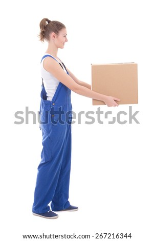 side view of young attractive woman in blue coveralls giving cardboard box isolated on white background