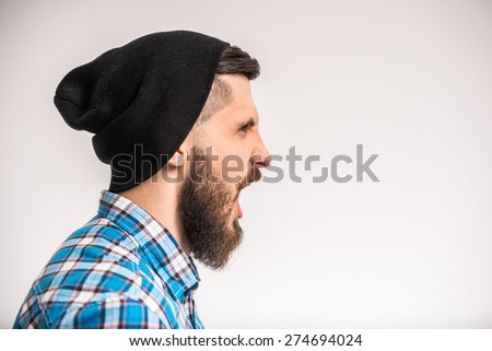 Side view of young bearded man is shouting standing on gray background. - stock photo