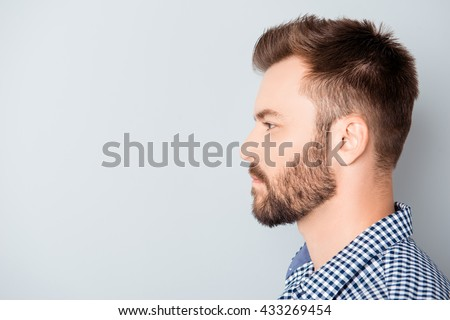 Side view of young bearded man isolated on gray background - stock photo