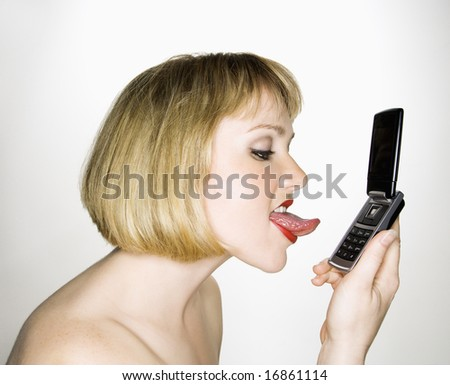 Side view of young blonde caucasian woman who is about to lick her cell phone. - stock photo