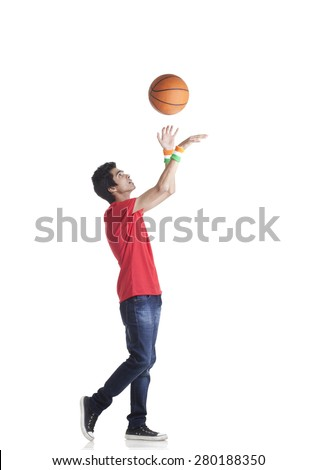 Side view of young boy in casuals tossing basketball over white background - stock photo