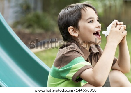 Side view of young boy on slide using inhaler in park - stock photo