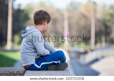 Side view of young boy sitting lotus position on granite curb - stock photo