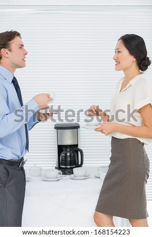Side view of young business couple with tea cups chatting in the office