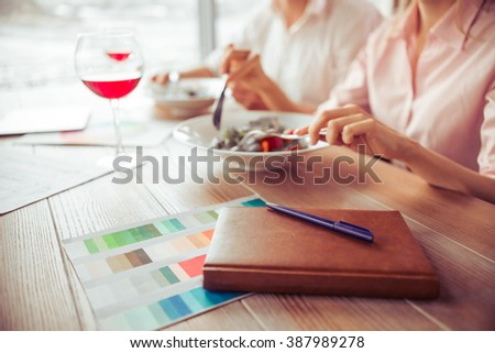 Side view of young business man and woman discussing business affairs during business lunch at the restaurant, close-up - stock photo