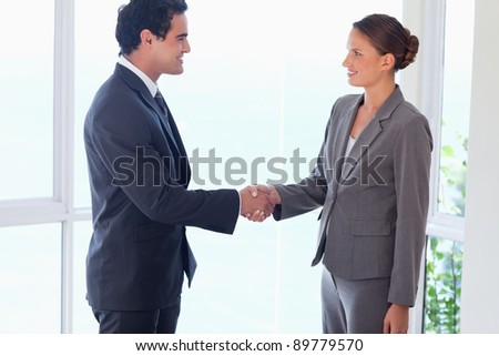 Side view of young business partner shaking hands - stock photo