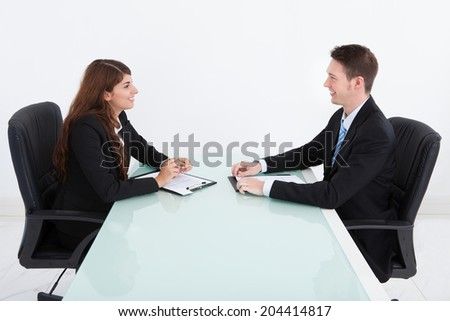 Side view of young businessman and businesswoman in meeting at office
