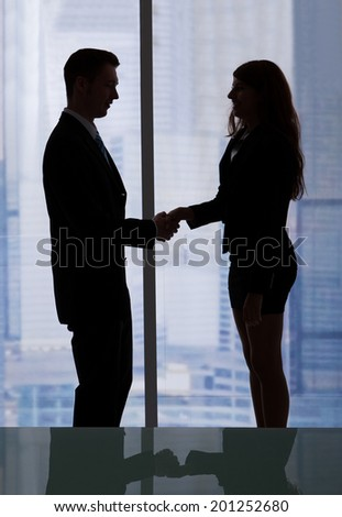 Side view of young businessman and businesswoman shaking hands in office