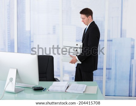 Side view of young businessman carrying stacked binders at office desk - stock photo