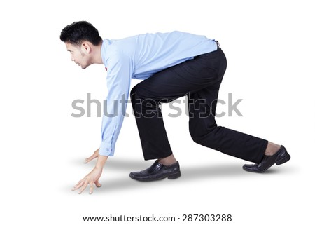 Side view of young businessman in ready position to race and compete, isolated on white