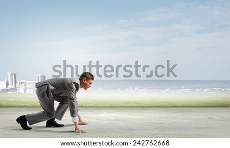 Side view of young businessman in start position ready to run - stock photo