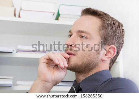 Side view of young businessman thinking in office - stock photo