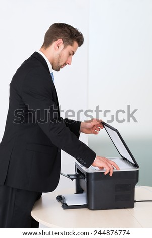 Side view of young businessman using photocopy machine in office - stock photo